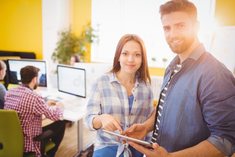Πορτρέτο των βέβαιων επιχειρηματιών που χρησιμοποιούν τον υπολογιστή ταμπλετών στο δημιουργικό γραφείο στοκ εικόνες