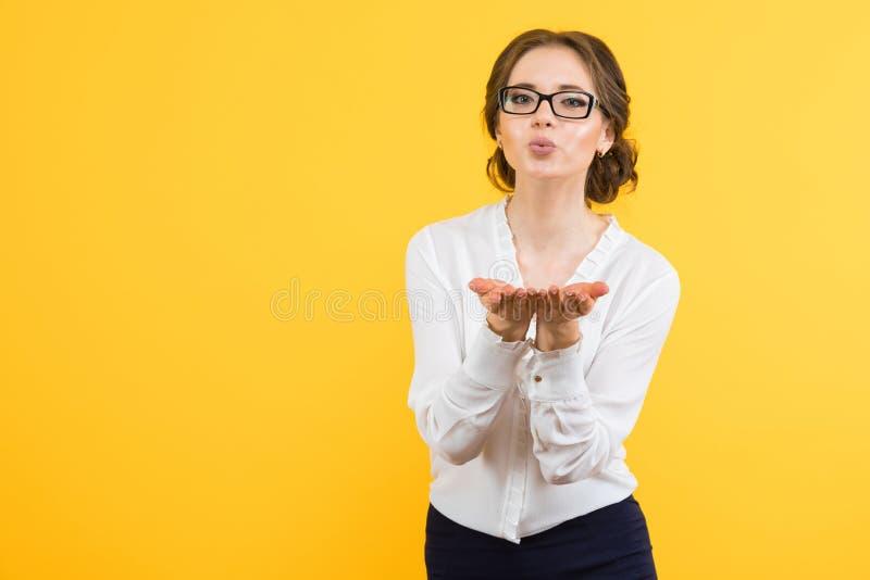 Πορτρέτο των βέβαιων όμορφων νεολαιών που χαμογελούν την ευτυχή επιχειρησιακή γυναίκα που στέλνει ένα φιλί αέρα στο κίτρινο υπόβα στοκ εικόνα με δικαίωμα ελεύθερης χρήσης