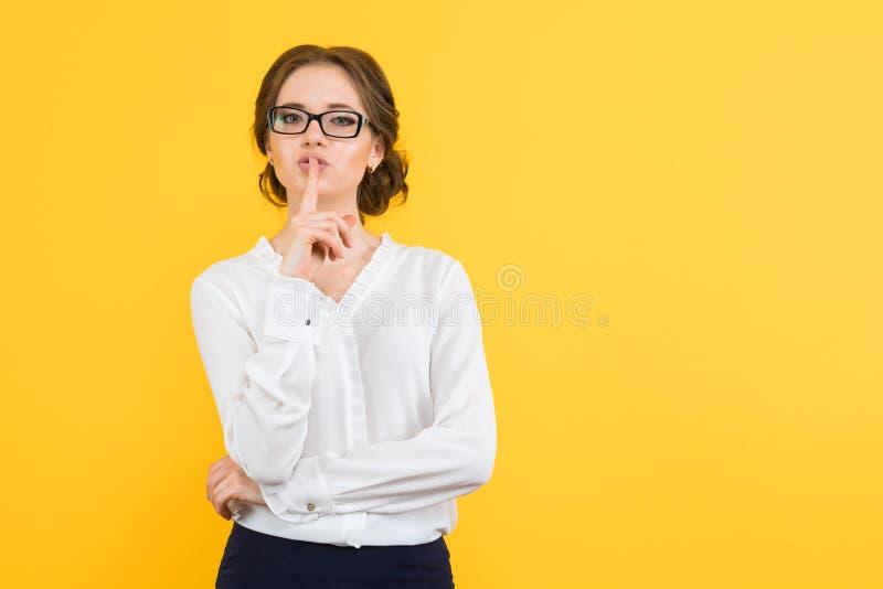 Πορτρέτο των βέβαιων όμορφων νεολαιών που χαμογελούν την ευτυχή επιχειρησιακή γυναίκα που κρατά το μυστικό στο κίτρινο υπόβαθρο στοκ εικόνα με δικαίωμα ελεύθερης χρήσης