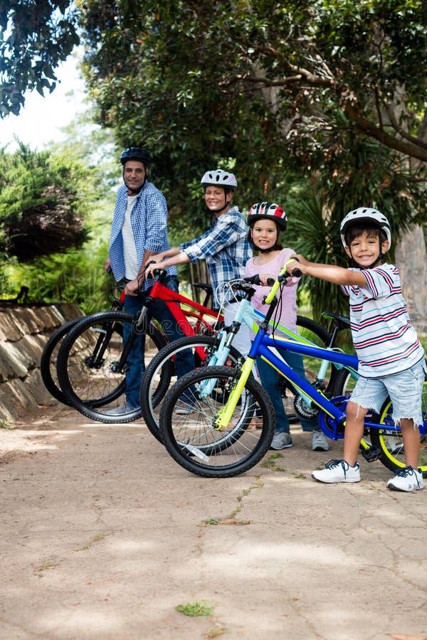 Πορτρέτο των γονέων και των παιδιών που στέκονται με το ποδήλατο στο πάρκο στοκ εικόνες