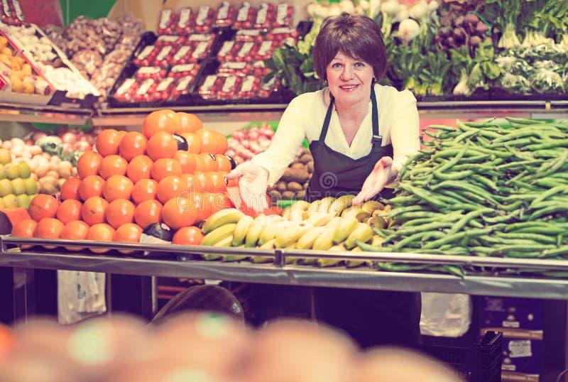 Πορτρέτο των ενήλικων θηλυκών πωλώντας φρούτων και λαχανικών στοκ φωτογραφία
