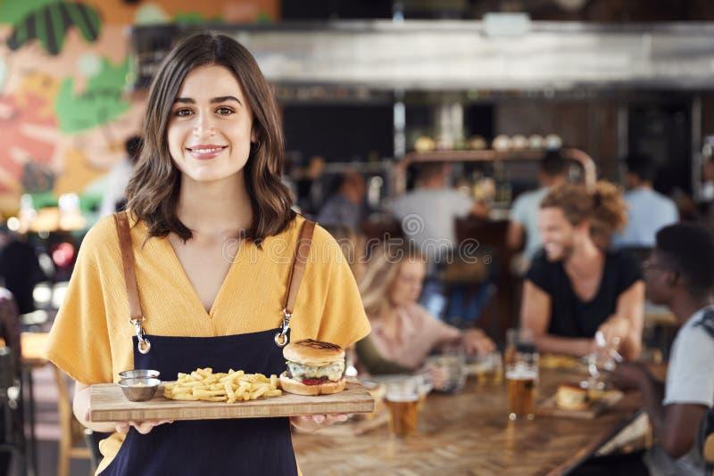 Πορτρέτο των εξυπηρετώντας τροφίμων σερβιτορών στους πελάτες στο πολυάσχολο εστιατόριο φραγμών στοκ φωτογραφία με δικαίωμα ελεύθερης χρήσης