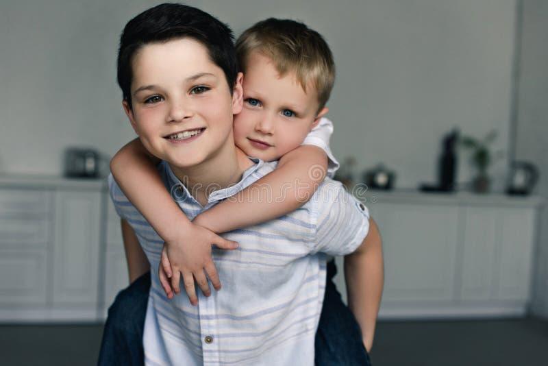 πορτρέτο των ευτυχών αδελφών piggybacking από κοινού στοκ φωτογραφία με δικαίωμα ελεύθερης χρήσης
