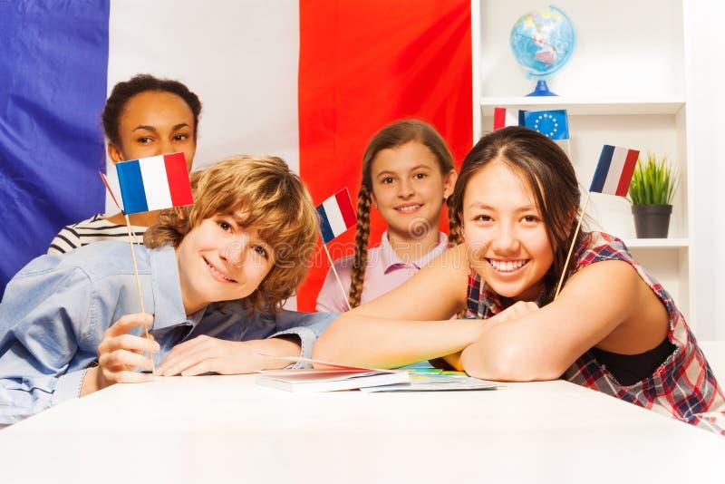 Πορτρέτο των ευτυχών εφηβικών σπουδαστών που κρατούν τις σημαίες στοκ εικόνες