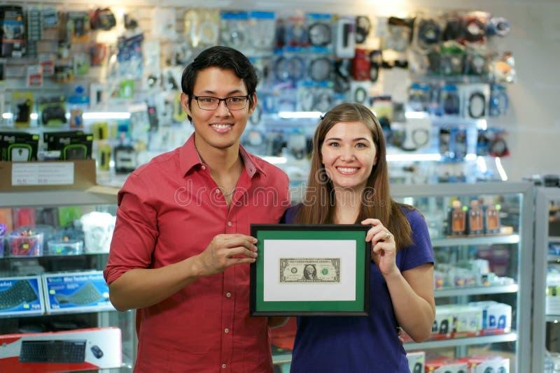 Πορτρέτο των ευτυχών ιδιοκτητών μαγαζιό που παρουσιάζουν πρώτη απόκτηση δολαρίων στοκ εικόνες με δικαίωμα ελεύθερης χρήσης
