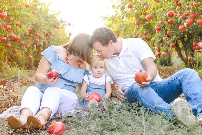 Πορτρέτο των ευτυχών χαμογελώντας και laughting γονέων με τη χαριτωμένη κόρη μωρών που έχει τη διασκέδαση στον κήπο φρούτων pomeg στοκ φωτογραφίες με δικαίωμα ελεύθερης χρήσης