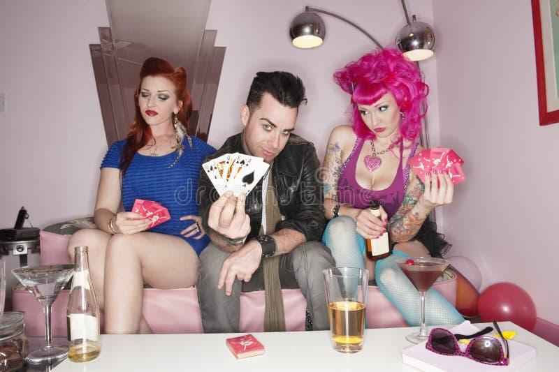 Πορτρέτο των καρτών παιχνιδιού εκμετάλλευσης ανδρών με τις γυναίκες που κάθονται εκτός από τον στοκ εικόνα με δικαίωμα ελεύθερης χρήσης