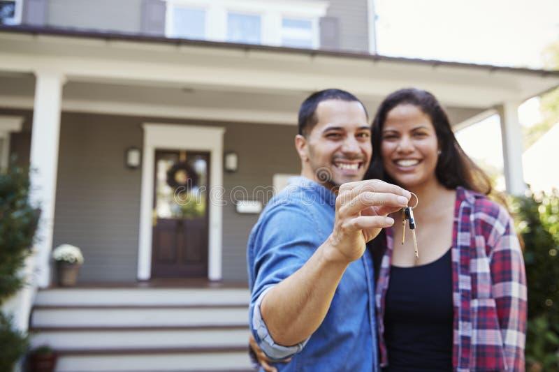 Πορτρέτο των κλειδιών εκμετάλλευσης ζεύγους για το νέο σπίτι στην κίνηση στην ημέρα στοκ φωτογραφίες