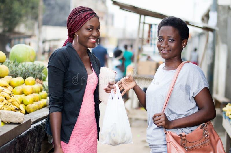 Πορτρέτο των νέων χαμογελώντας γυναικών που στέκονται στην αγορά φρούτων στοκ εικόνα
