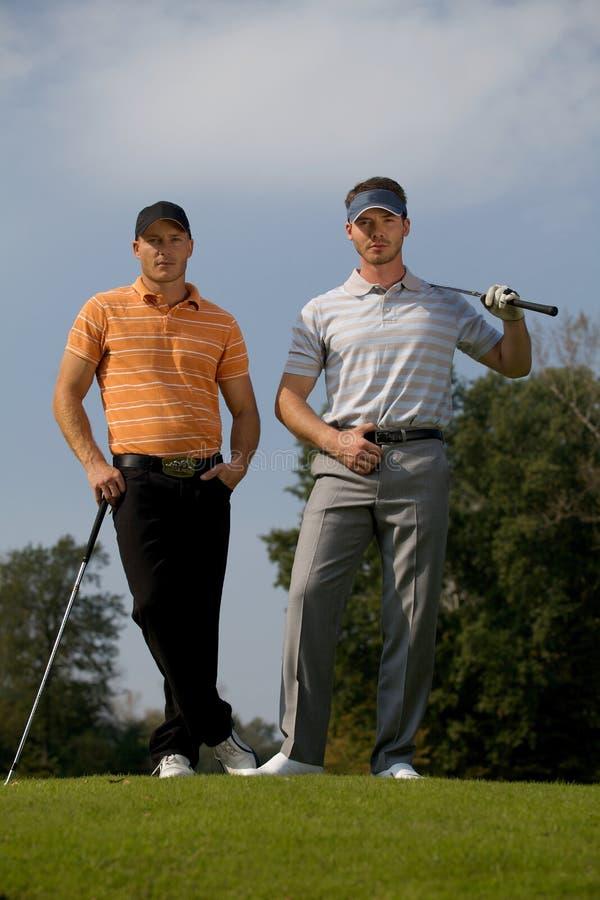Πορτρέτο των νεαρών άνδρων που στέκονται με τα ραβδιά γκολφ στο γήπεδο του γκολφ στοκ φωτογραφίες με δικαίωμα ελεύθερης χρήσης