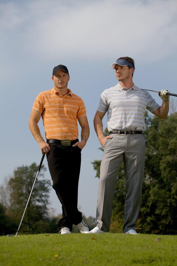 Πορτρέτο των νεαρών άνδρων που στέκονται με τα ραβδιά γκολφ στο γήπεδο του γκολφ στοκ φωτογραφία με δικαίωμα ελεύθερης χρήσης