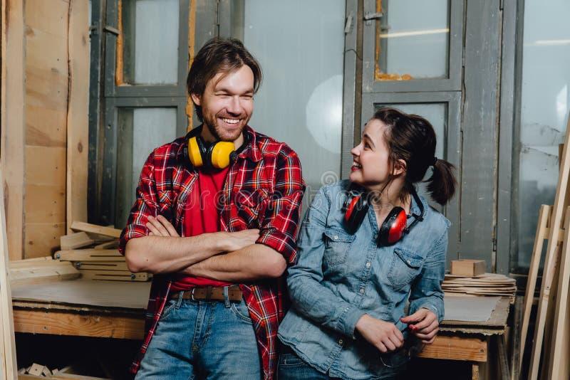 Πορτρέτο των ξυλουργών στο εργαστήριο Ένα άτομο και ένα κορίτσι, έκλιναν πίσω και έθεσαν στοκ φωτογραφίες με δικαίωμα ελεύθερης χρήσης