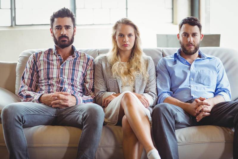 Πορτρέτο των σοβαρών επιχειρηματιών που κάθονται στον καναπέ στοκ εικόνες