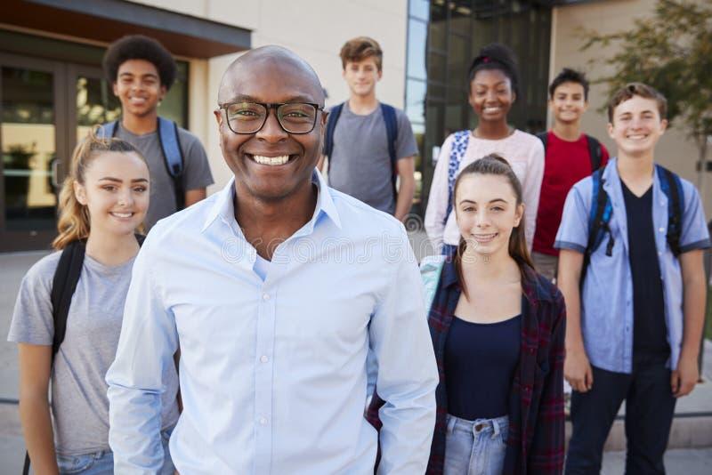 Πορτρέτο των σπουδαστών γυμνασίου με το δάσκαλο έξω από τα κτήρια κολλεγίου στοκ εικόνα με δικαίωμα ελεύθερης χρήσης