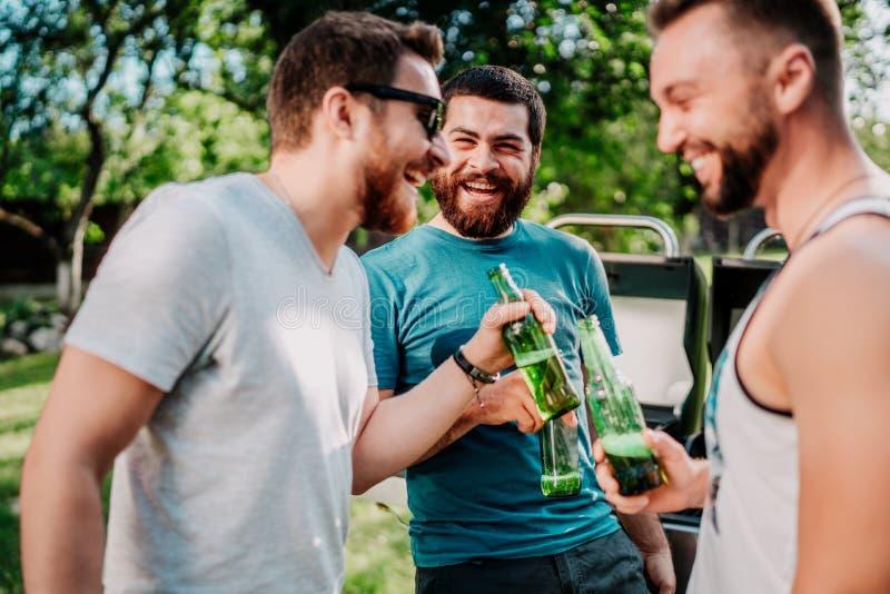 Πορτρέτο των τύπων γέλιου που έχουν μια σχάρα κήπων, που ψήνουν στη σχάρα και που μαγειρεύουν, έχοντας τις οινοπνευματώδεις μπύρε στοκ εικόνες