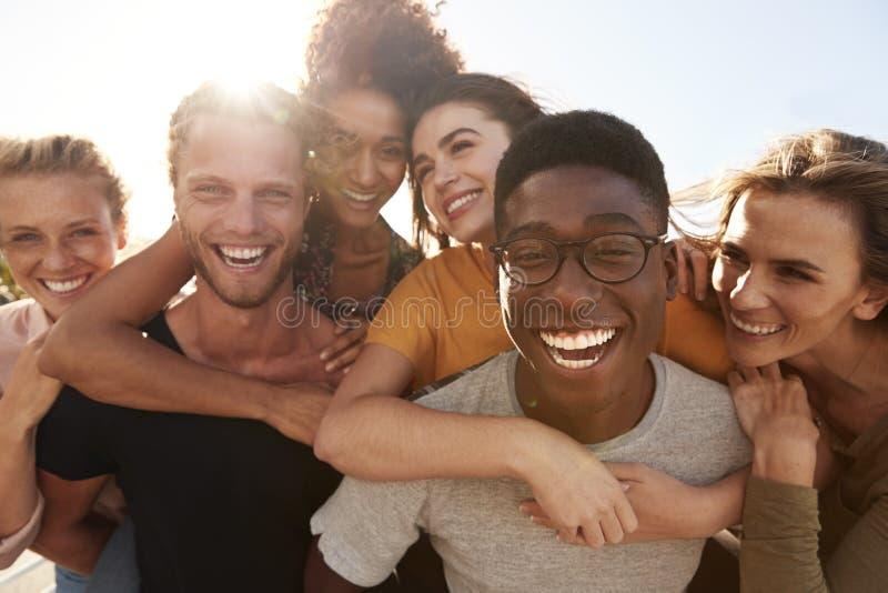 Πορτρέτο των χαμογελώντας νέων φίλων που περπατούν υπαίθρια από κοινού στοκ εικόνα με δικαίωμα ελεύθερης χρήσης