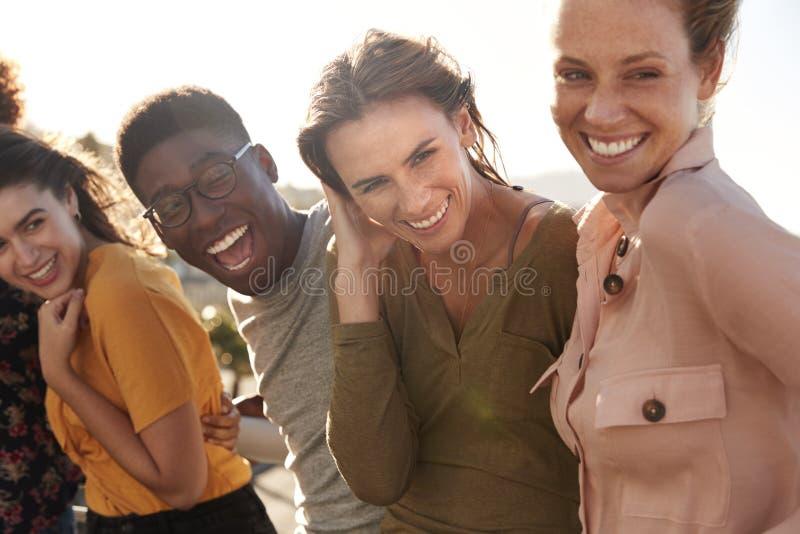 Πορτρέτο των χαμογελώντας νέων φίλων που περπατούν υπαίθρια από κοινού στοκ φωτογραφίες