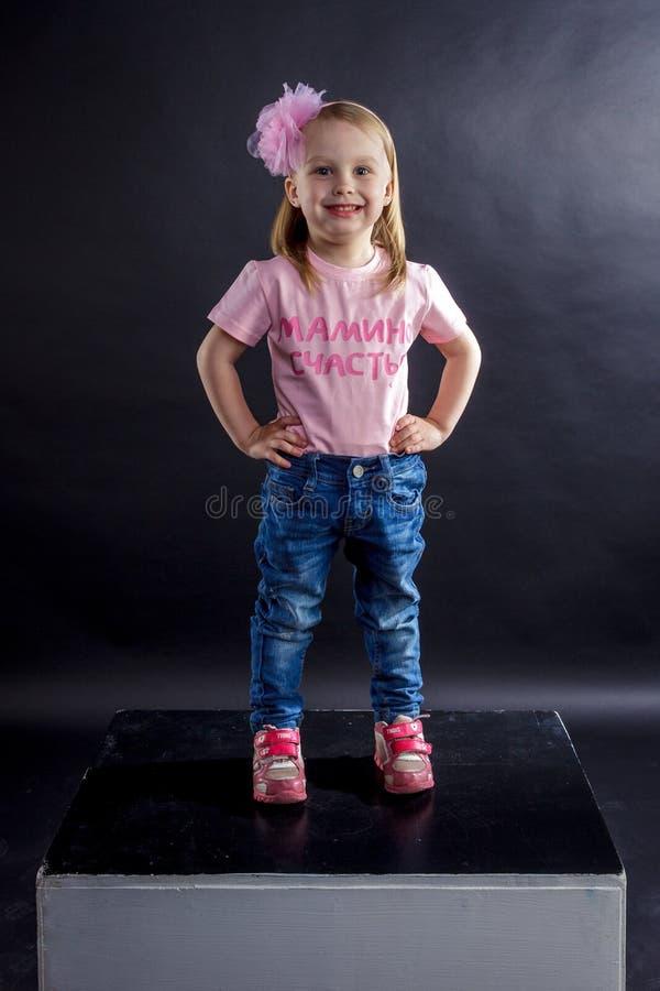 Πορτρέτο των χαριτωμένων ευρωπαϊκών μικρών ξανθών κοριτσιών στα τζιν και της ρόδινης μπλούζας με την επιγραφή: στοκ εικόνες