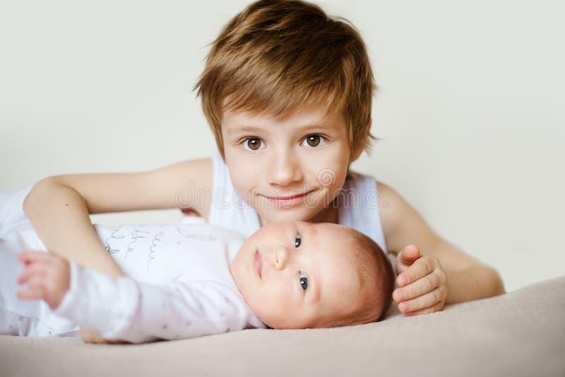 Πορτρέτο των χαριτωμένων ευτυχών αμφιθαλών νέο αγόρι που κρατά το μωρό νηπίων του στοκ φωτογραφίες