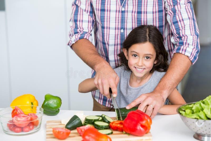 Πορτρέτο των χαριτωμένων τεμνόντων λαχανικών κορών με τον πατέρα στοκ φωτογραφία
