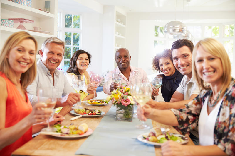 Πορτρέτο των ώριμων φίλων γύρω από τον πίνακα στο κόμμα γευμάτων στοκ εικόνες