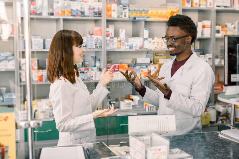 Πορτρέτο των multiethnical αρσενικών και θηλυκών φαρμακοποιών που στέκονται κοντά στο μετρητή, την ομιλία, το γέλιο και φαρμακείω στοκ φωτογραφία