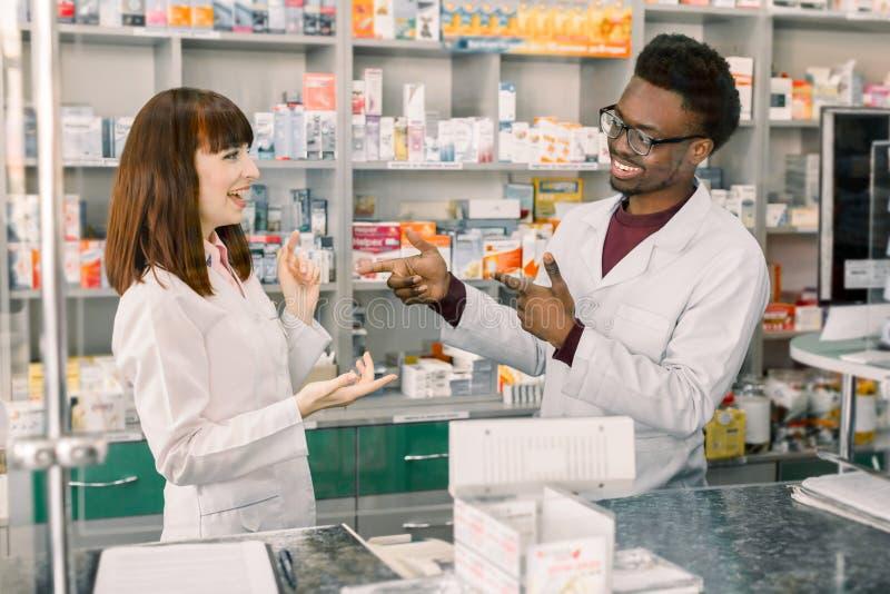 Πορτρέτο των multiethnical αρσενικών και θηλυκών φαρμακοποιών που στέκονται κοντά στο μετρητή, την ομιλία, το γέλιο και φαρμακείω στοκ εικόνες