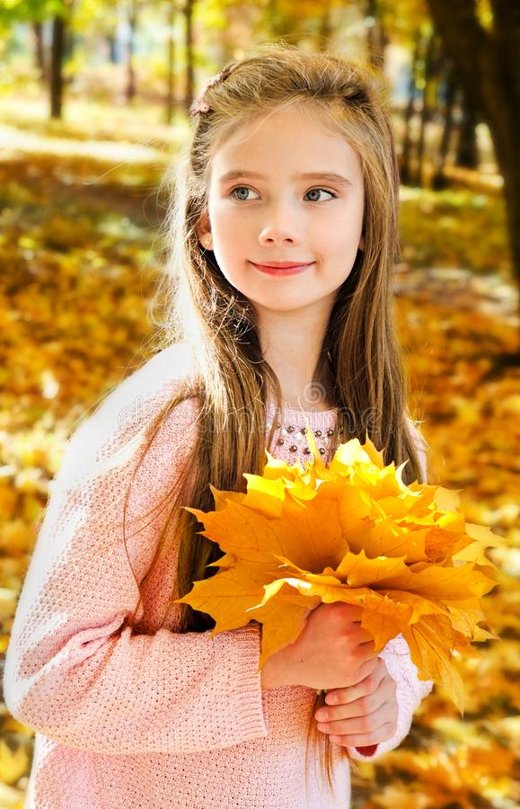 Πορτρέτο φθινοπώρου του λατρευτού χαμογελώντας παιδιού μικρών κοριτσιών με τα φύλλα στοκ φωτογραφία με δικαίωμα ελεύθερης χρήσης