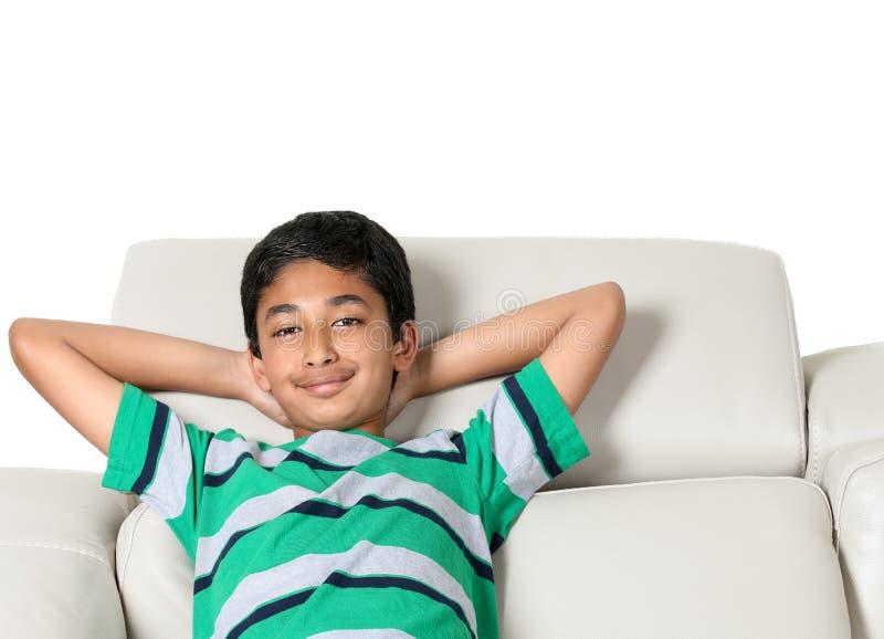 Πορτρέτο χαμόγελου ενός νέου αγοριού σε έναν καναπέ στοκ φωτογραφία με δικαίωμα ελεύθερης χρήσης