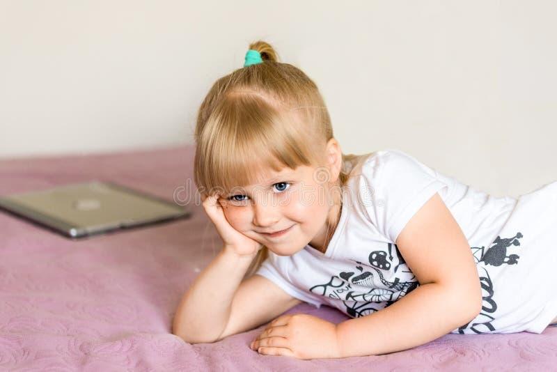 Πορτρέτο χαριτωμένο λίγου ξανθού καυκάσιου κοριτσιού που ονειρεύεται για κάτι στο κρεβάτι με την πορφυρή κάλυψη Το κορίτσι έχει τ στοκ φωτογραφία
