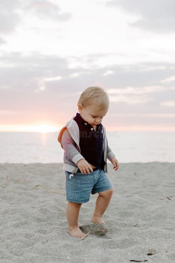 Πορτρέτο χαριτωμένο λίγου παιδιού αγοράκι που παίζει και που εξερευνά στην άμμο στην παραλία κατά τη διάρκεια του ηλιοβασιλέματος στοκ εικόνες