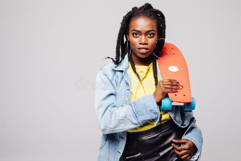 Πορτρέτο χαριτωμένο skateboard εκμετάλλευσης γυναικών χαμόγελου αφρικανικό και εξέταση τη κάμερα που απομονώνεται πέρα από το γκρ στοκ φωτογραφίες