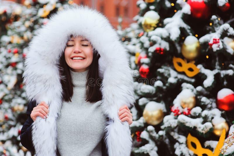 Πορτρέτο Χριστουγέννων του ευτυχούς νέου περπατήματος γυναικών στη χειμερινή χιονώδη πόλη στοκ εικόνες