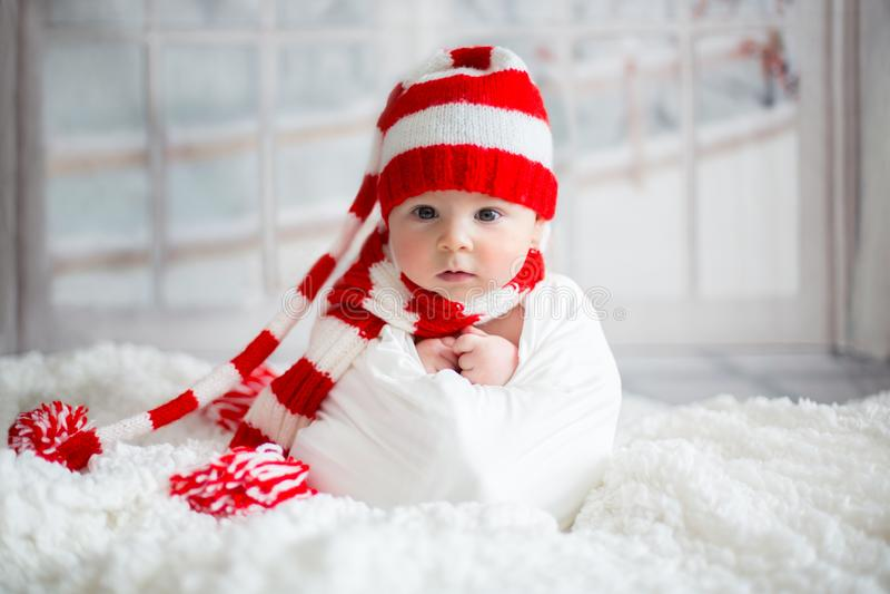 Πορτρέτο Χριστουγέννων χαριτωμένου λίγο νεογέννητο αγοράκι, που φορά sant στοκ εικόνες
