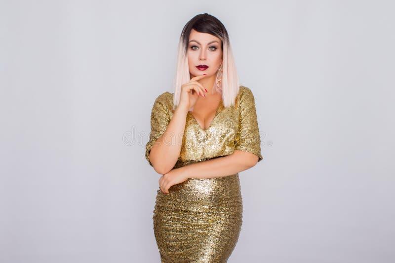 Πορτρέτο όμορφου ενός ξανθού με το φωτεινό makeup σε ένα χρυσό φόρεμα στοκ εικόνες με δικαίωμα ελεύθερης χρήσης