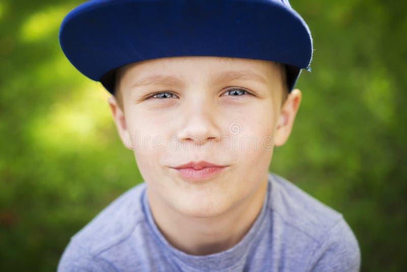 Πορτρέτο όμορφου λίγο λευκό αγόρι στην ΚΑΠ στο πράσινο θερινό πάρκο την ηλιόλουστη ημέρα στοκ εικόνα
