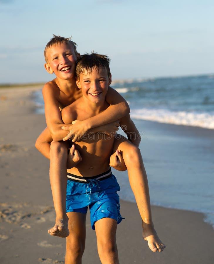 Πορτρέτο δύο ευτυχών παιδιών που παίζουν στην παραλία στο θερινό vacati στοκ εικόνες
