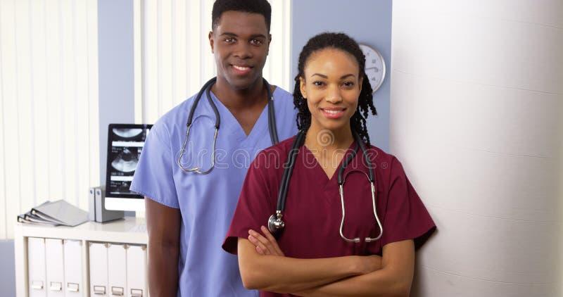 Πορτρέτο δύο ιατρικών ειδικών αφροαμερικάνων που στέκονται στο νοσοκομείο στοκ φωτογραφία
