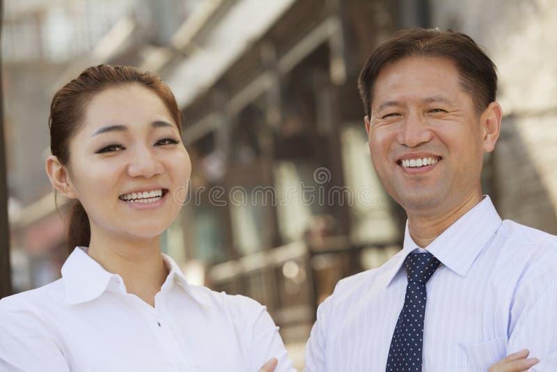 Πορτρέτο δύο χαμογελώντας επιχειρηματιών που εξετάζουν τη κάμερα, υπαίθρια, Πεκίνο στοκ φωτογραφία με δικαίωμα ελεύθερης χρήσης