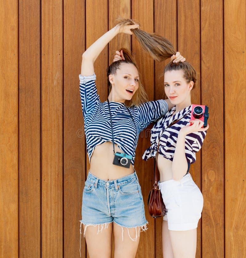 Πορτρέτο δύο όμορφων μοντέρνων φίλων στα σορτς τζιν και τη ριγωτή τοποθέτηση μπλουζών Κορίτσι που κρατά την από την τρίχα Outdoo στοκ φωτογραφία με δικαίωμα ελεύθερης χρήσης