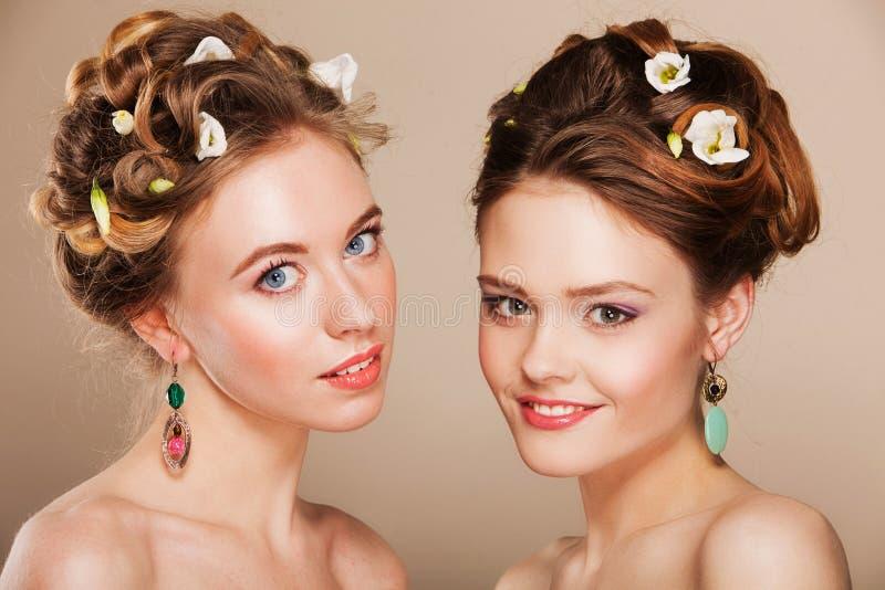 Πορτρέτο δύο όμορφων νέων γυναικών με το τέλειο makeup και hairstyle τη φθορά του κοσμήματος στοκ φωτογραφίες