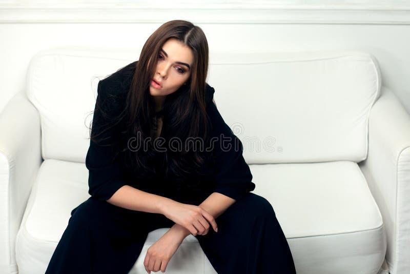 Πορτρέτο ύφους μόδας της όμορφης γυναίκας brunette σε έναν καναπέ στοκ φωτογραφία