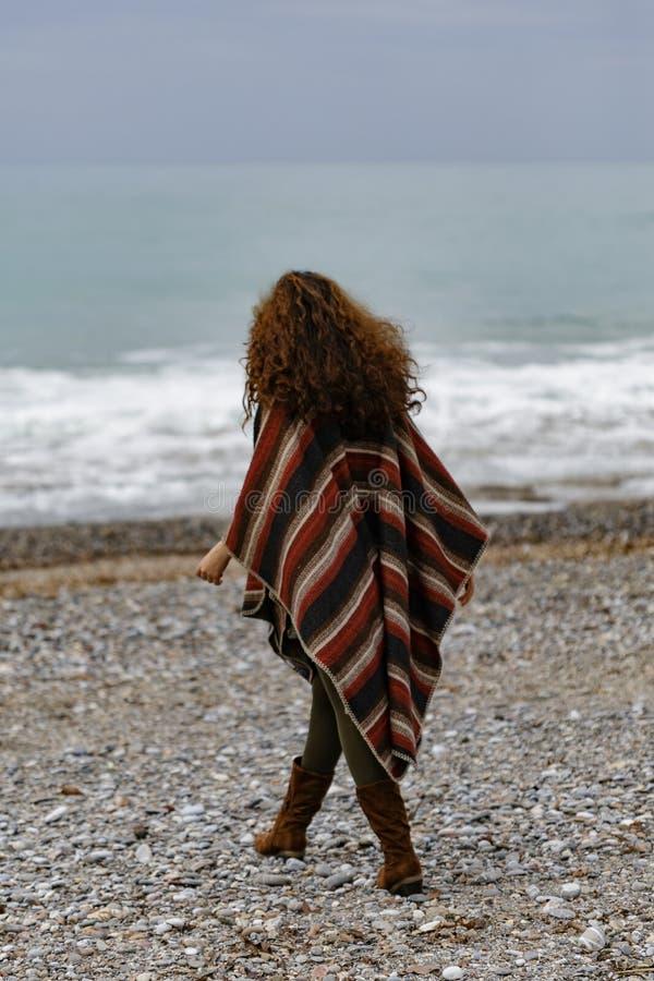Πορτρέτο Backview της ευτυχούς γυναίκας brunette στην παραλία που φορά το π στοκ εικόνα