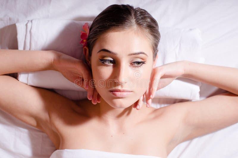 Πορτρέτο SPA της νέας όμορφης γυναίκας με τη ορχιδέα που βρίσκεται σε την πίσω και που χαλαρώνει με τους γυμνούς ώμους που φαίνον στοκ εικόνα