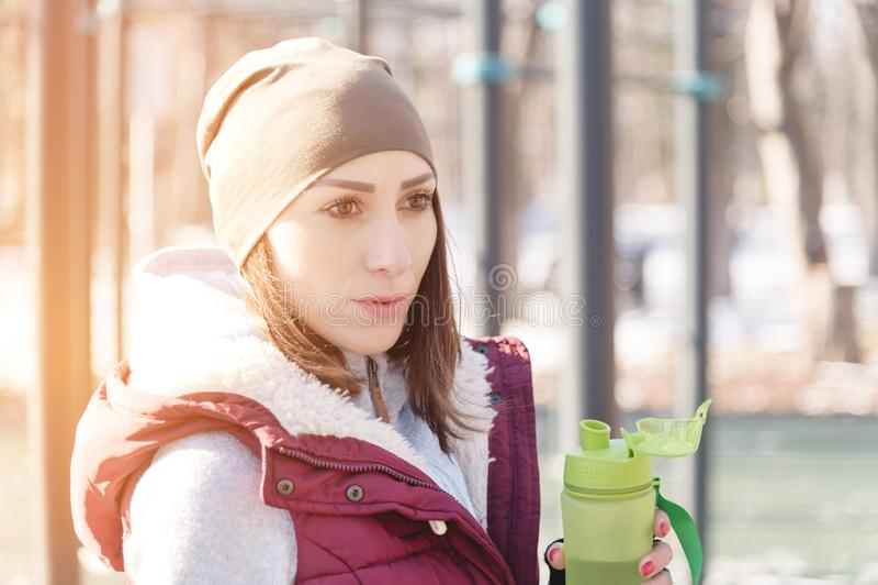 Πορτραίτο αθλητικής κοπέλας που κάνει γυμναστική το χειμώνα σε υπαίθριο αθλητικό γήπεδο Ποτά νερό αποβάλλει δίψα στοκ φωτογραφίες