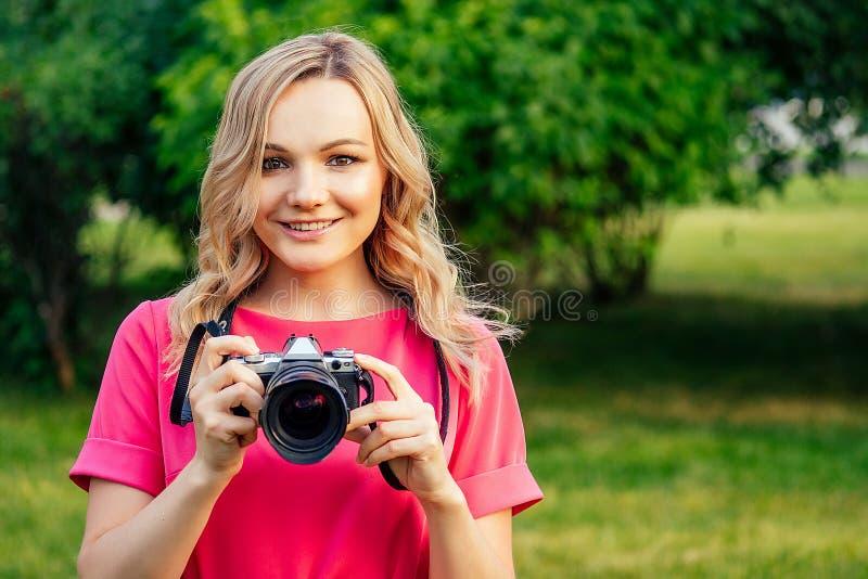 Πορτραίτο φωτογραφικής επαγγελματικής όμορφης νεαρής ξανθιάς γυναίκας με ροζ φόρεμα φωτογραφισμένο στο θερινό πάρκο στοκ φωτογραφία με δικαίωμα ελεύθερης χρήσης