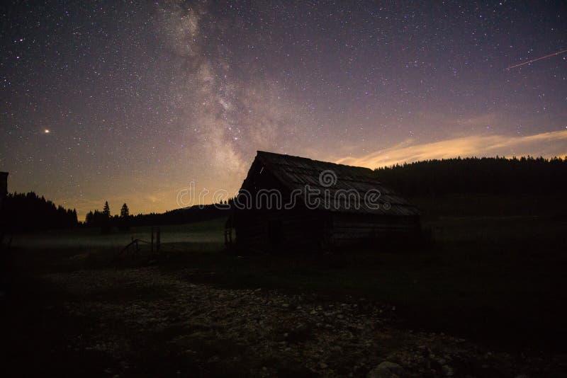 Πορφυρά αστέρια νυχτερινού ουρανού πέρα από το βουνό και το παλαιό ξύλινο σπίτι Γαλακτώδης γαλαξίας τρόπων στη θερινή έναστρη νύχ στοκ εικόνες