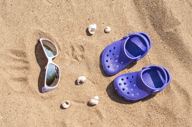 Πορφυρά clog και γυαλιά ηλίου μωρών στην άμμο στην παραλία Χαριτωμένες λεπτομέρειες των καλοκαιρινών διακοπών Παπούτσια μωρών στη στοκ εικόνα με δικαίωμα ελεύθερης χρήσης