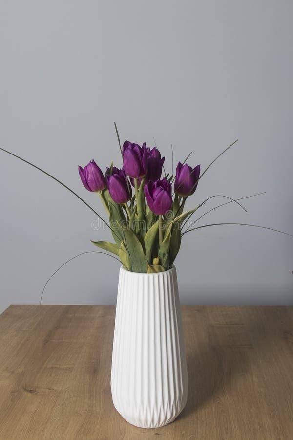 Πορφυρή ανθοδέσμη λουλουδιών τουλιπών σε ένα άσπρο δοχείο σύγχρονου σ στοκ φωτογραφία με δικαίωμα ελεύθερης χρήσης