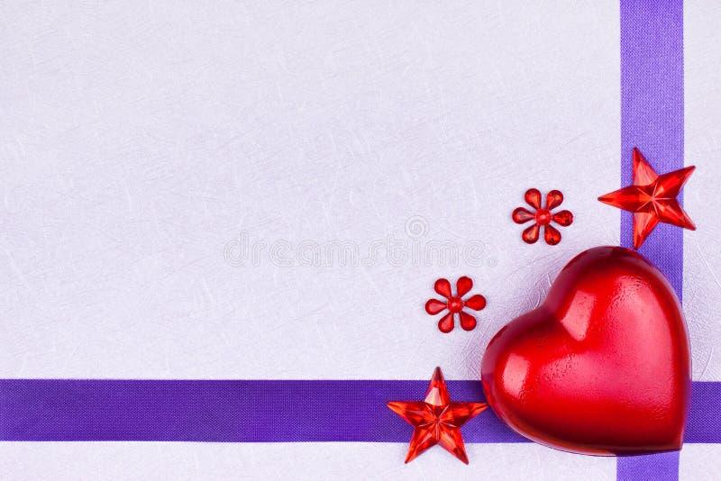 Πορφυρή ευχετήρια κάρτα με την κόκκινη καρδιά στοκ εικόνα